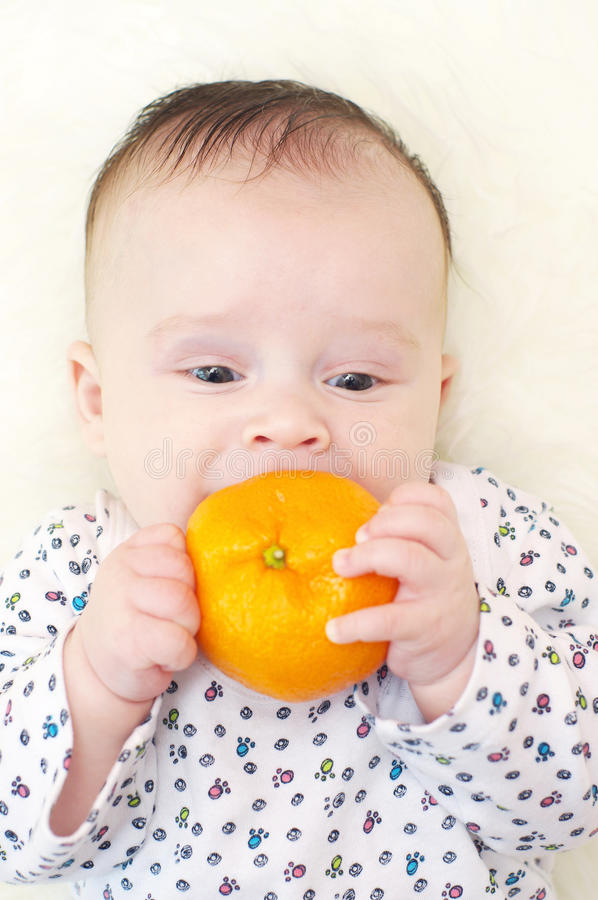 La edad del bebé de 3 meses muerde la mandarina imágenes de archivo libres de regalías