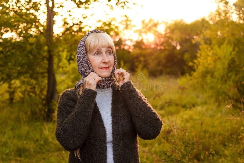 La edad del retiro femenina atractiva ajusta su pañuelo en el contraluz foto de archivo libre de regalías