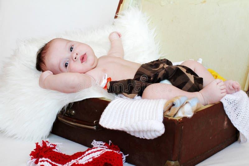 La edad feliz del bebé de 3 meses miente en una maleta con ropa imagen de archivo