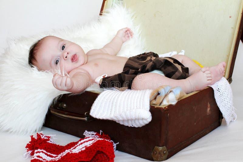 La edad preciosa del bebé de 3 meses miente en una maleta con ropa imagenes de archivo