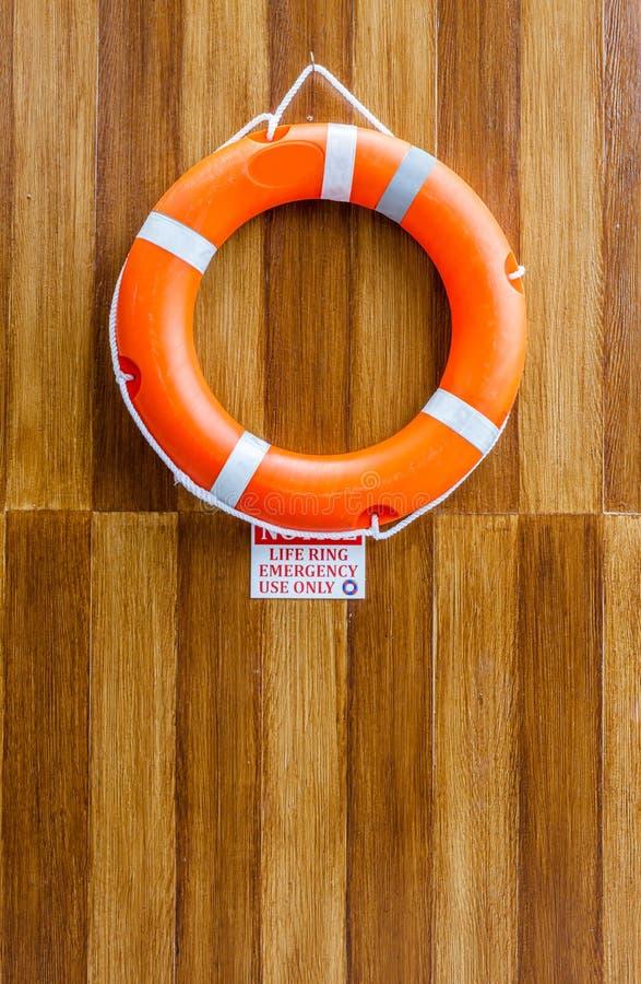 La ejecución anaranjada de la boya de vida en la pared de madera para la seguridad y el re fotografía de archivo libre de regalías