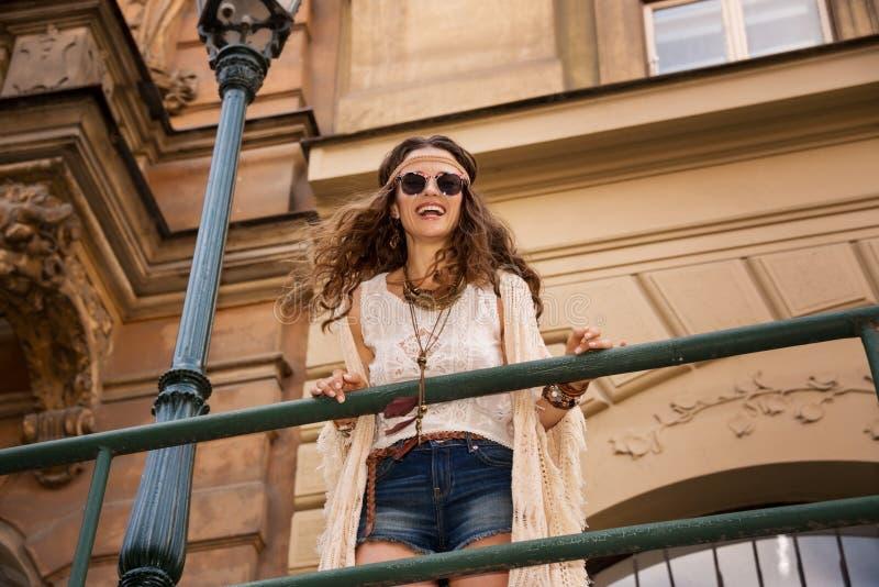 La elegancia de pelo largo del boho con las gafas de sol acerca a la farola vieja de la ciudad foto de archivo libre de regalías