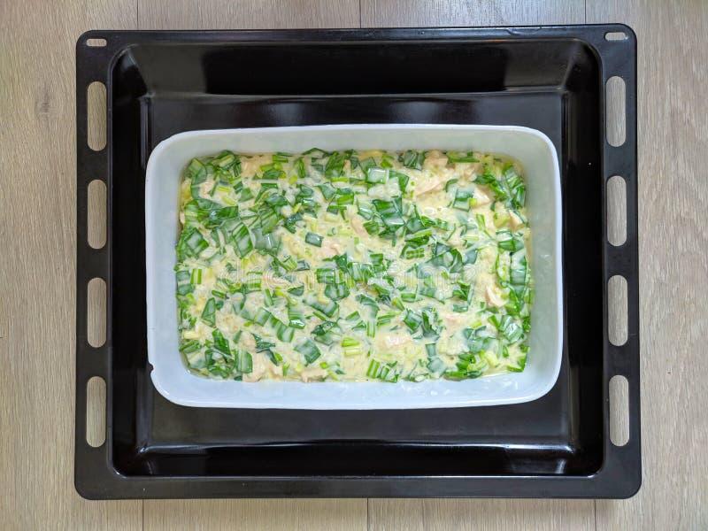 La empanada cruda con la cebolla verde cortó lanzamientos adentro baken el asador antes de la hornada Fondo de madera beige liger imagenes de archivo