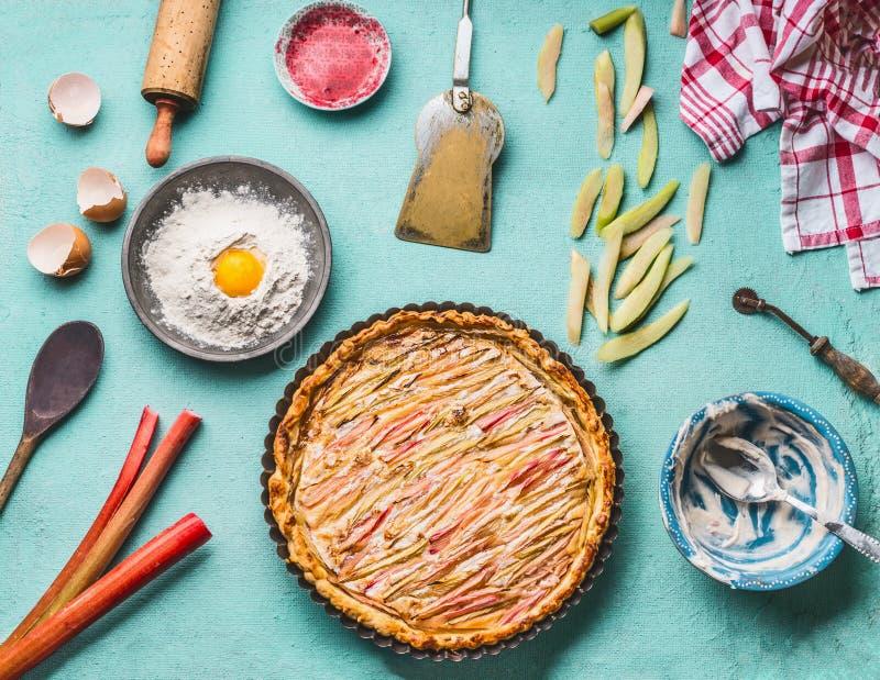 La empanada de ruibarbo hecha en casa con los ingredientes en fondo azul de tabla de cocina con cuece el utensilio, la harina y e foto de archivo