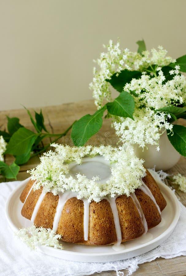 La empanada del limón con un esmalte del azúcar y el elderflower concentran, adornado con las flores de la baya del saúco Estilo  imagen de archivo