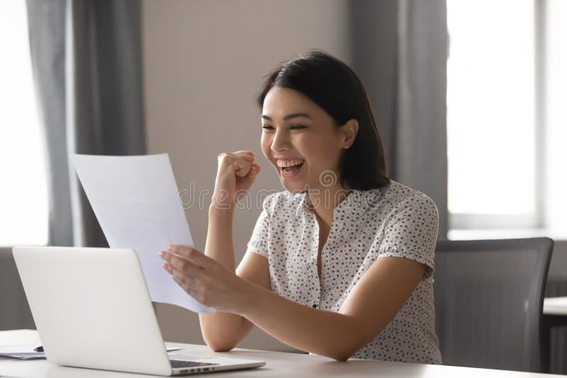 La empresaria asiática feliz celebra el éxito que mira informe financiero fotos de archivo