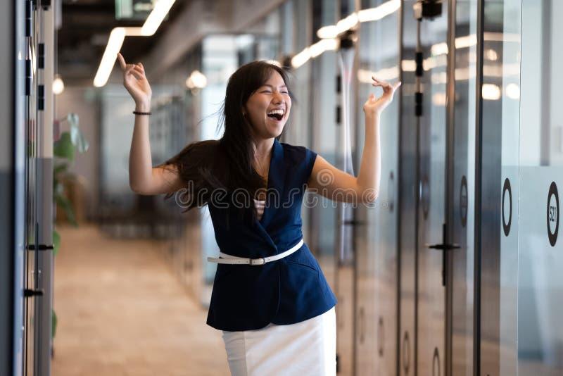 La empresaria asiática joven divertida emocionada celebra éxito en danza de la victoria foto de archivo libre de regalías
