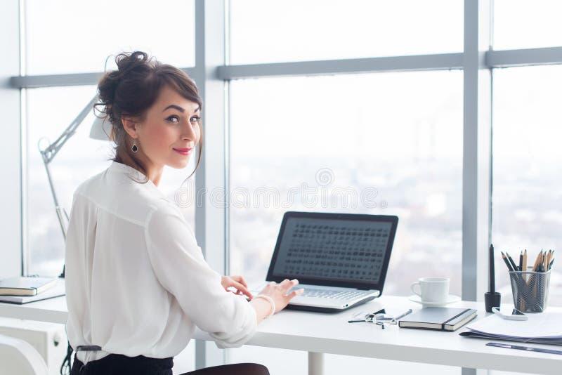 La empresaria atractiva que trabaja en la oficina usando la PC, buscando y estudiando ideas del negocio en un ordenador portátil  fotos de archivo libres de regalías