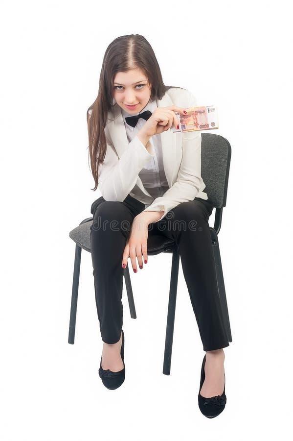 La empresaria bonita con las rublos se sienta en silla imagenes de archivo