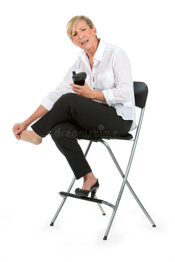 La empresaria con los pies doloridos se sentó en una silla imagenes de archivo
