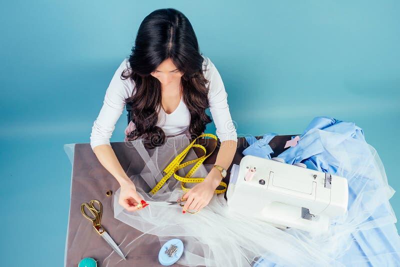 La empresaria de brunette costurera de confección trabaja en el taller con máquina de coser y cinta dosificadora en un taller fotografía de archivo libre de regalías
