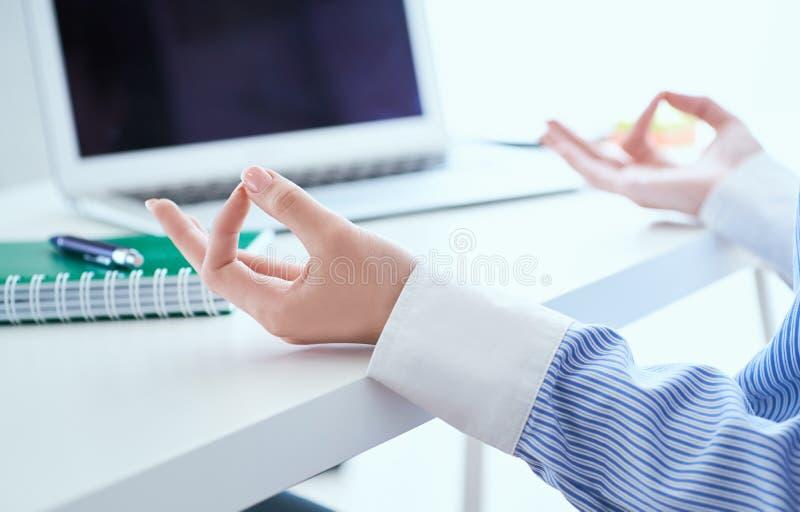 La empresaria de la calma que medita en el trabajo, foco en las manos femeninas en mudra, se cierra encima de la visi?n Empleado  imagen de archivo libre de regalías