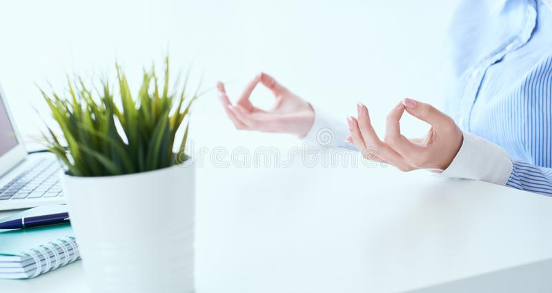 La empresaria de la calma que medita en el trabajo, foco en las manos femeninas en mudra, se cierra encima de la visi?n Empleado  foto de archivo