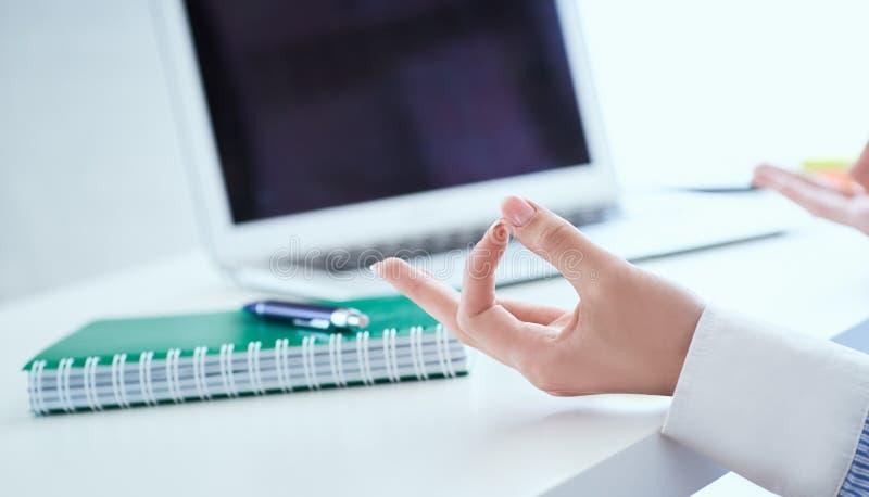La empresaria de la calma que medita en el trabajo, foco en las manos femeninas en mudra, se cierra encima de la visi?n Empleado  imagen de archivo