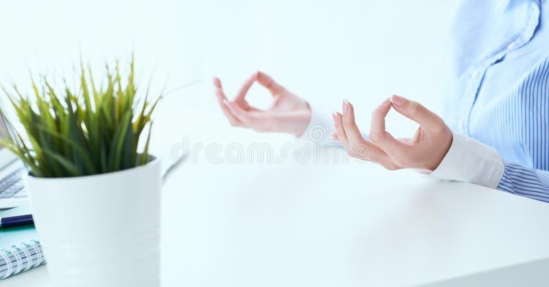 La empresaria de la calma que medita en el trabajo, foco en las manos femeninas en mudra, se cierra encima de la visi?n Empleado  foto de archivo libre de regalías
