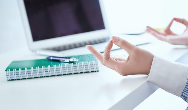 La empresaria de la calma que medita en el trabajo, foco en las manos femeninas en mudra, se cierra encima de la visi?n Empleado  fotografía de archivo libre de regalías