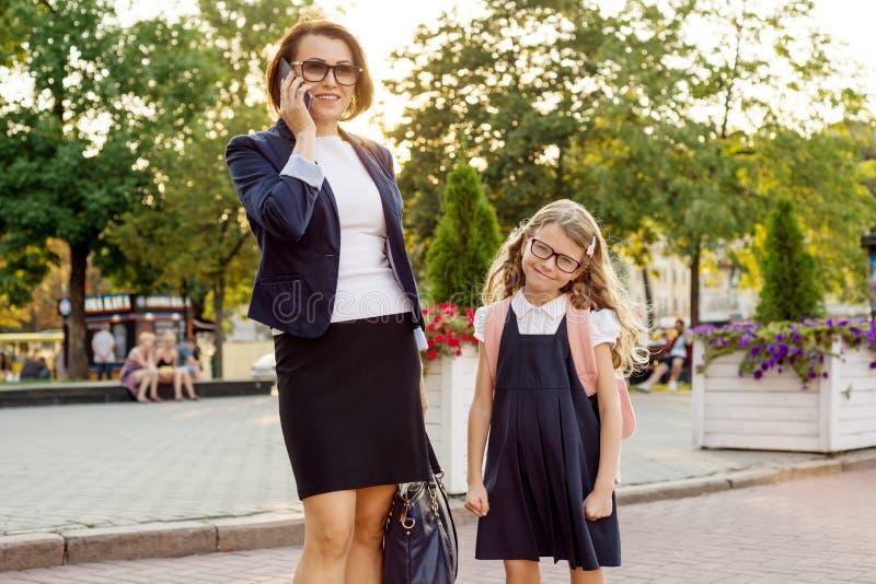 La empresaria de la mamá lleva al niño a la escuela imagen de archivo