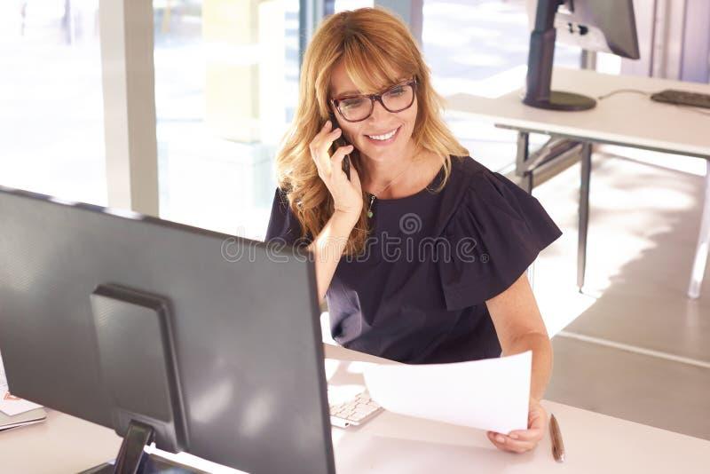 La empresaria ejecutiva da una llamada mientras que trabaja en la oficina fotos de archivo libres de regalías
