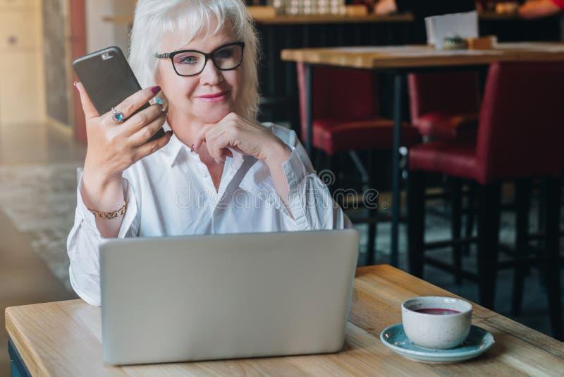 La empresaria en vidrios se está sentando en la tabla delante del ordenador portátil imagen de archivo libre de regalías