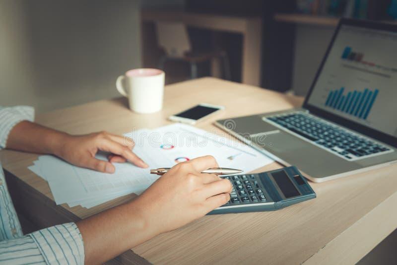 La empresaria es el analizar del cálculo financiero y de planificación para la inversión en la mesa de la tabla , Documento del i imagen de archivo