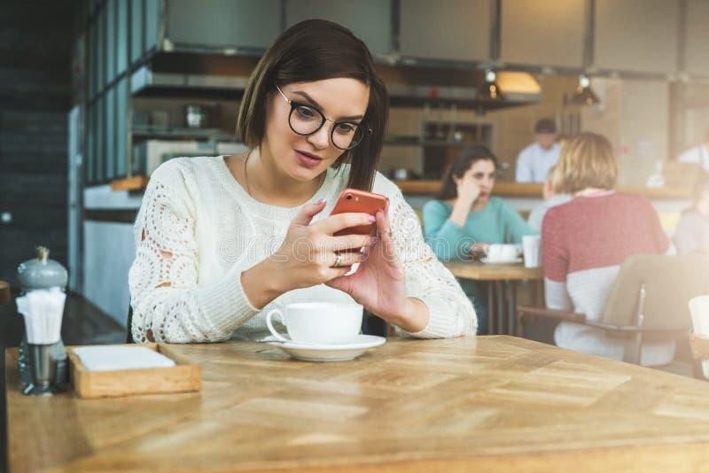 La empresaria feliz joven en vidrios y suéter se está sentando en café en la tabla y está utilizando el smartphone, trabajando Ap fotografía de archivo libre de regalías