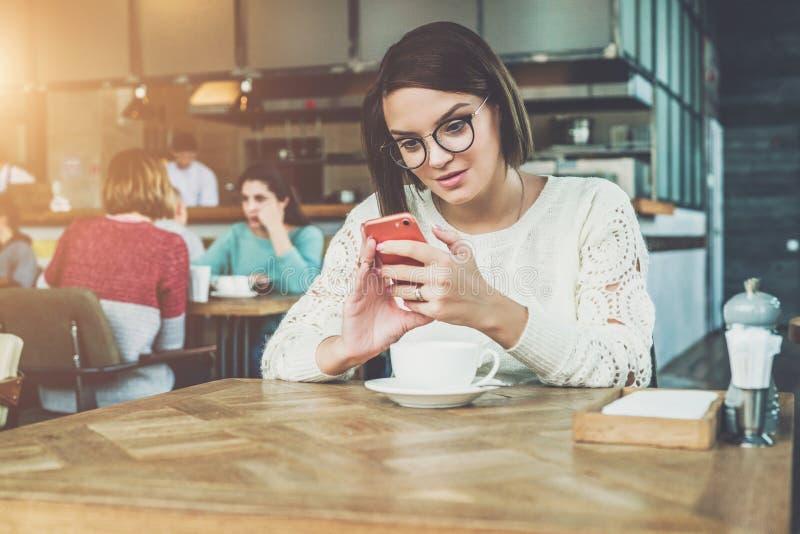 La empresaria feliz joven en vidrios y suéter se está sentando en café en la tabla y está utilizando el smartphone, trabajando Ap imagenes de archivo