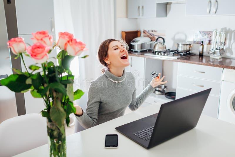 La empresaria feliz que gritaba con los brazos abrió el funcionamiento en el ordenador portátil en cocina en casa Freelancer emoc foto de archivo