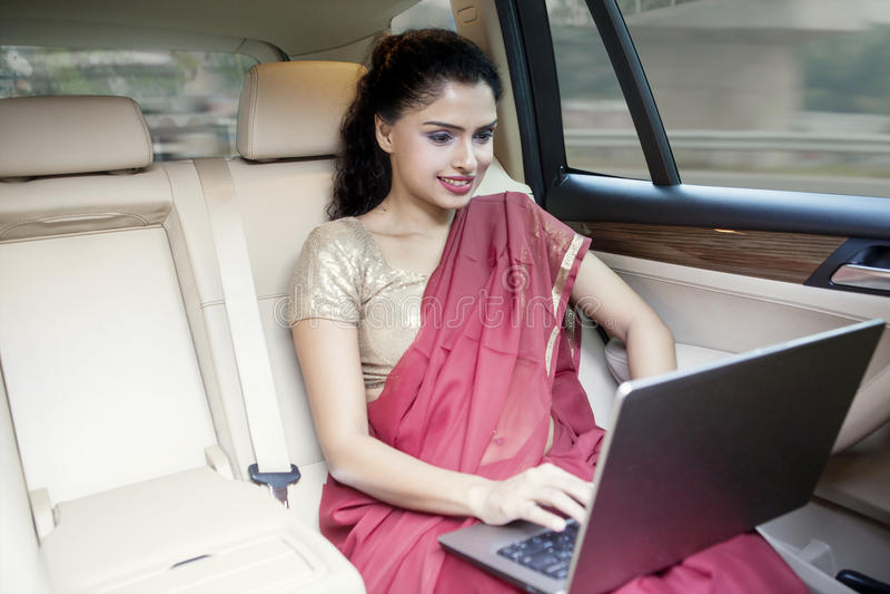 La empresaria india trabaja con el ordenador portátil en coche fotos de archivo