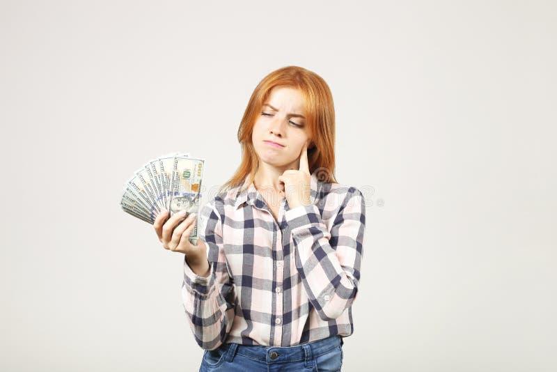 La empresaria joven atractiva que presenta con el manojo de USD aprovecha las manos que muestran emociones positivas y la expresi fotografía de archivo