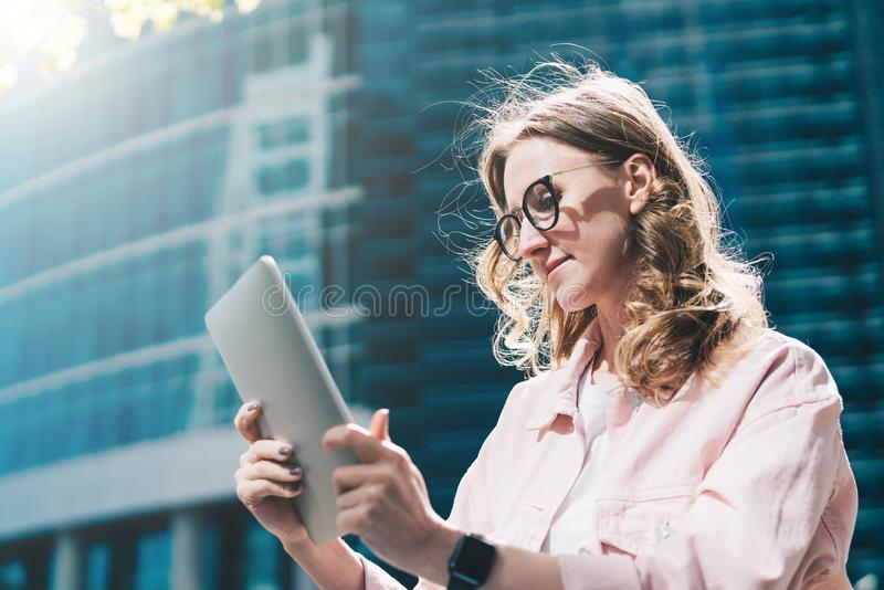 La empresaria joven del inconformista en vidrios está sosteniendo la tableta en sus manos y está leyendo la información en su pan imagen de archivo libre de regalías