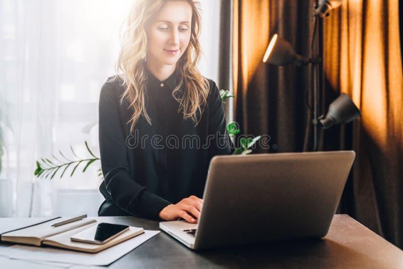 La empresaria joven en camisa negra se está sentando en la tabla, trabajando en el ordenador Cerca está el cuaderno, smartphone e imagen de archivo