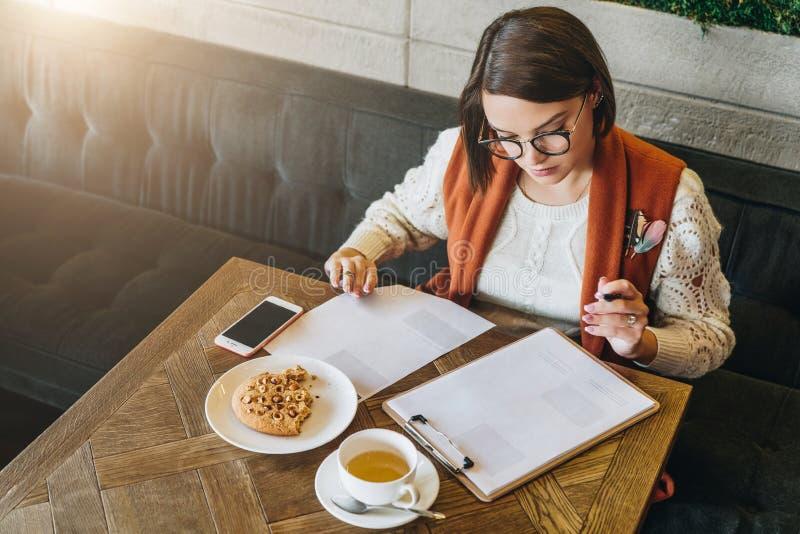 La empresaria joven en vidrios y el suéter blanco se está sentando en café en la tabla, documentos de firma, trabajando foto de archivo libre de regalías