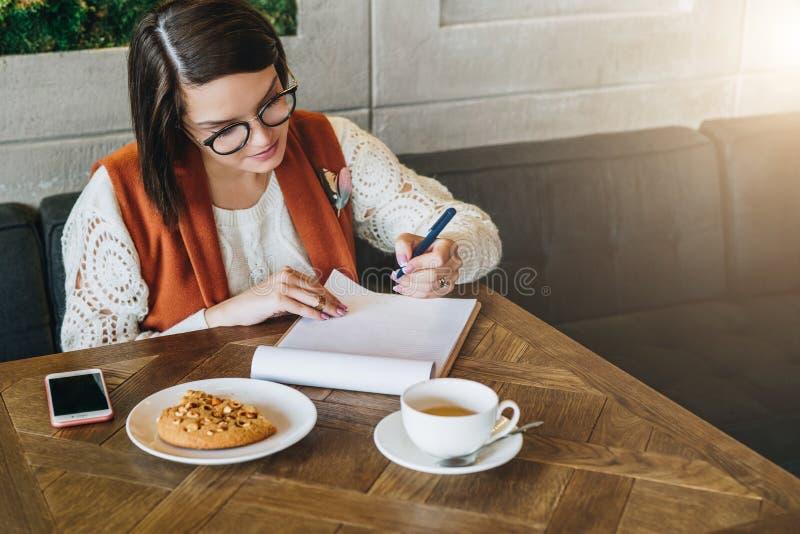 La empresaria joven en vidrios y el suéter blanco se está sentando en café en la tabla, trabajando La muchacha analiza datos foto de archivo