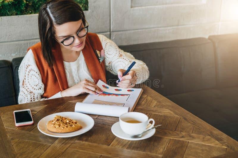 La empresaria joven en vidrios y el suéter blanco se está sentando en café en la tabla, trabajando La muchacha está mirando las c imagenes de archivo
