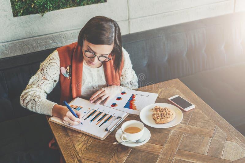La empresaria joven en vidrios y el suéter blanco se está sentando en café en la tabla, trabajando La mujer está mirando las cart imagenes de archivo
