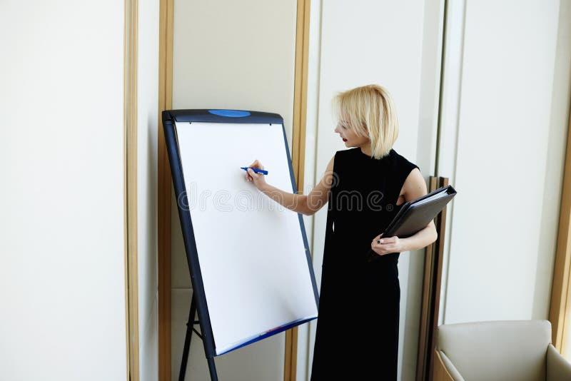La empresaria joven está trabajando con el personal fotografía de archivo