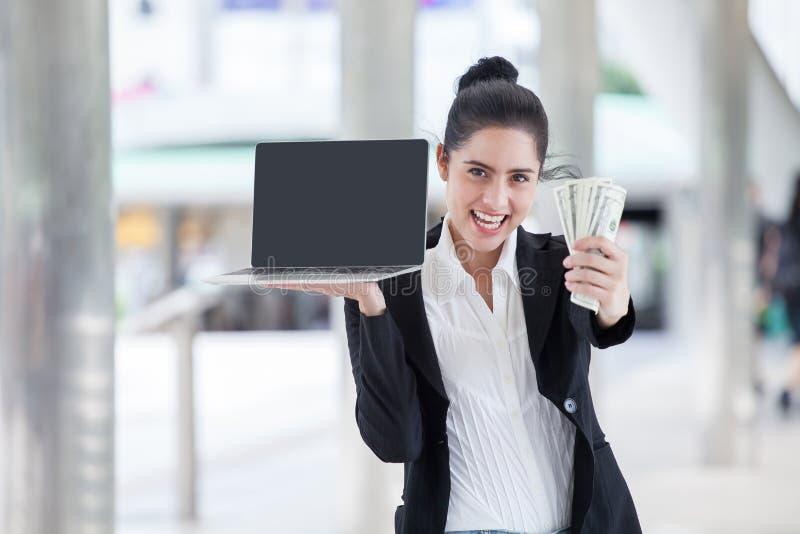 la empresaria joven feliz está mostrando el dinero y el ordenador portátil con la pantalla del espacio de la copia y la trayector fotos de archivo