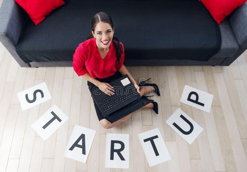 La empresaria joven hermosa que se sienta en el piso, usando una empresaria joven laptopBeautiful que usa un ordenador portátil,  imagen de archivo