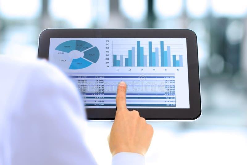 La empresaria joven que muestra gráficos por el finger en la tableta digital fotografía de archivo