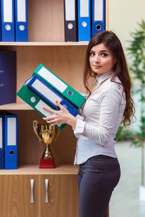 La empresaria joven que se coloca al lado de estante fotografía de archivo