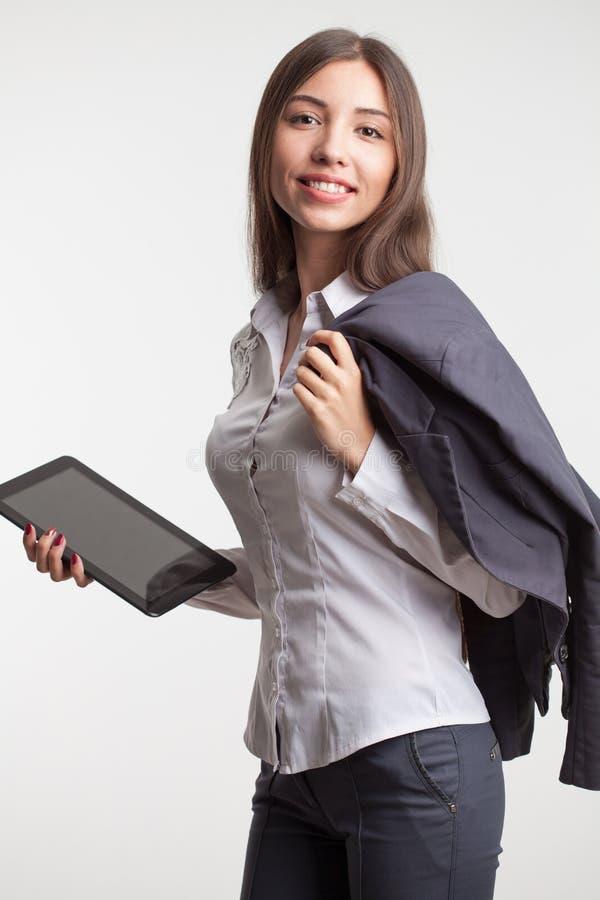 La empresaria joven sonriente que muestra ninguno-nombre en blanco hace tabletas el monitor de la PC con el área del copyspace pa imagen de archivo