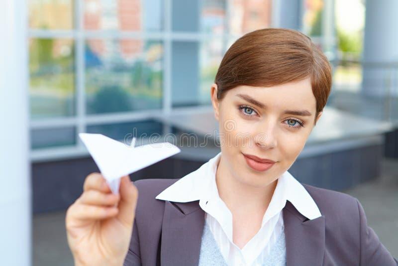 La empresaria lanza el aeroplano de papel. imagen de archivo libre de regalías
