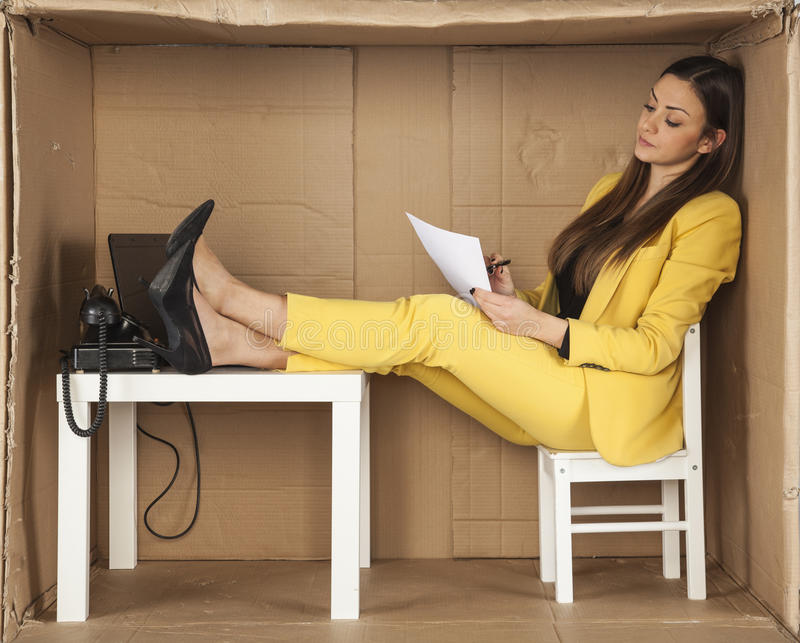 La empresaria lee documentos y guarda sus pies en el escritorio fotos de archivo