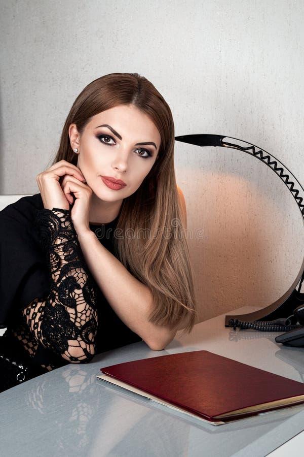 La empresaria, la muchacha o la mujer acertada hermosa en traje de negocios, se sienta en silla cerca de la tabla Concepto del ne imagenes de archivo