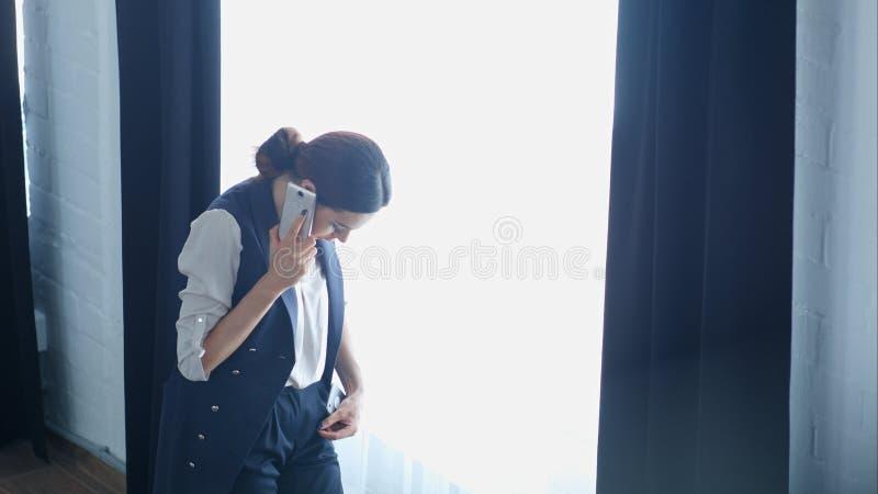La empresaria orgullosa joven está hablando en su teléfono móvil con el cliente, mientras que coloca la ventana cercana de la ofi imágenes de archivo libres de regalías