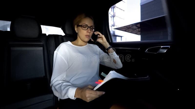 La empresaria que mira con el informe, conduciendo en coche, quita el control de la compañía fotografía de archivo