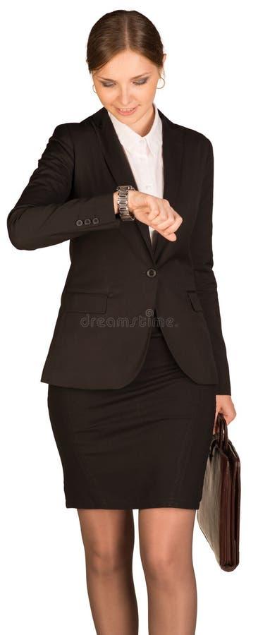 La empresaria que mira su reloj y mantiene imagen de archivo