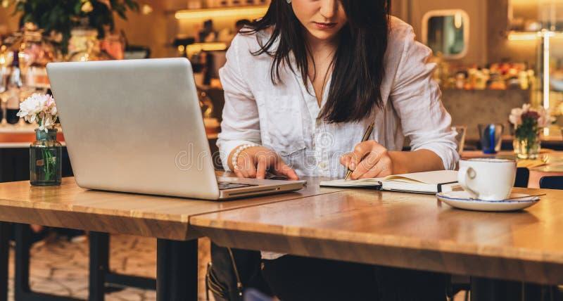 La empresaria se está sentando en café en la tabla delante del ordenador portátil, haciendo notas en el cuaderno, trabajando Estu imagen de archivo