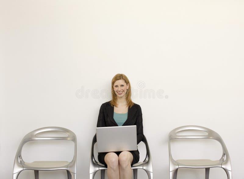 La empresaria se sienta con el ordenador portátil fotos de archivo