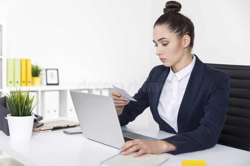 La empresaria seria está leyendo una nota fotos de archivo